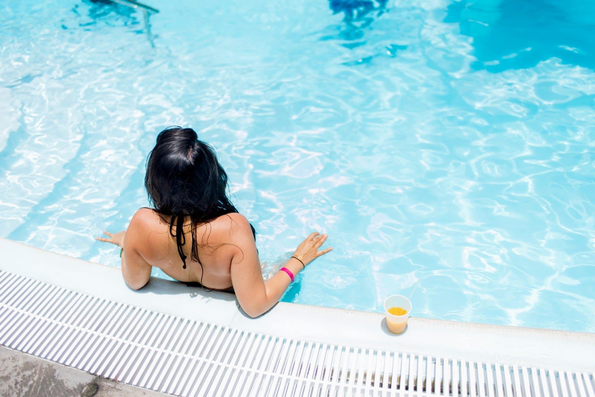 femme qui bronze au bord de la piscine