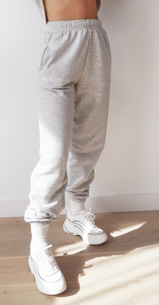 jogging tendance gris porté avec des chaussettes et baskets blanches