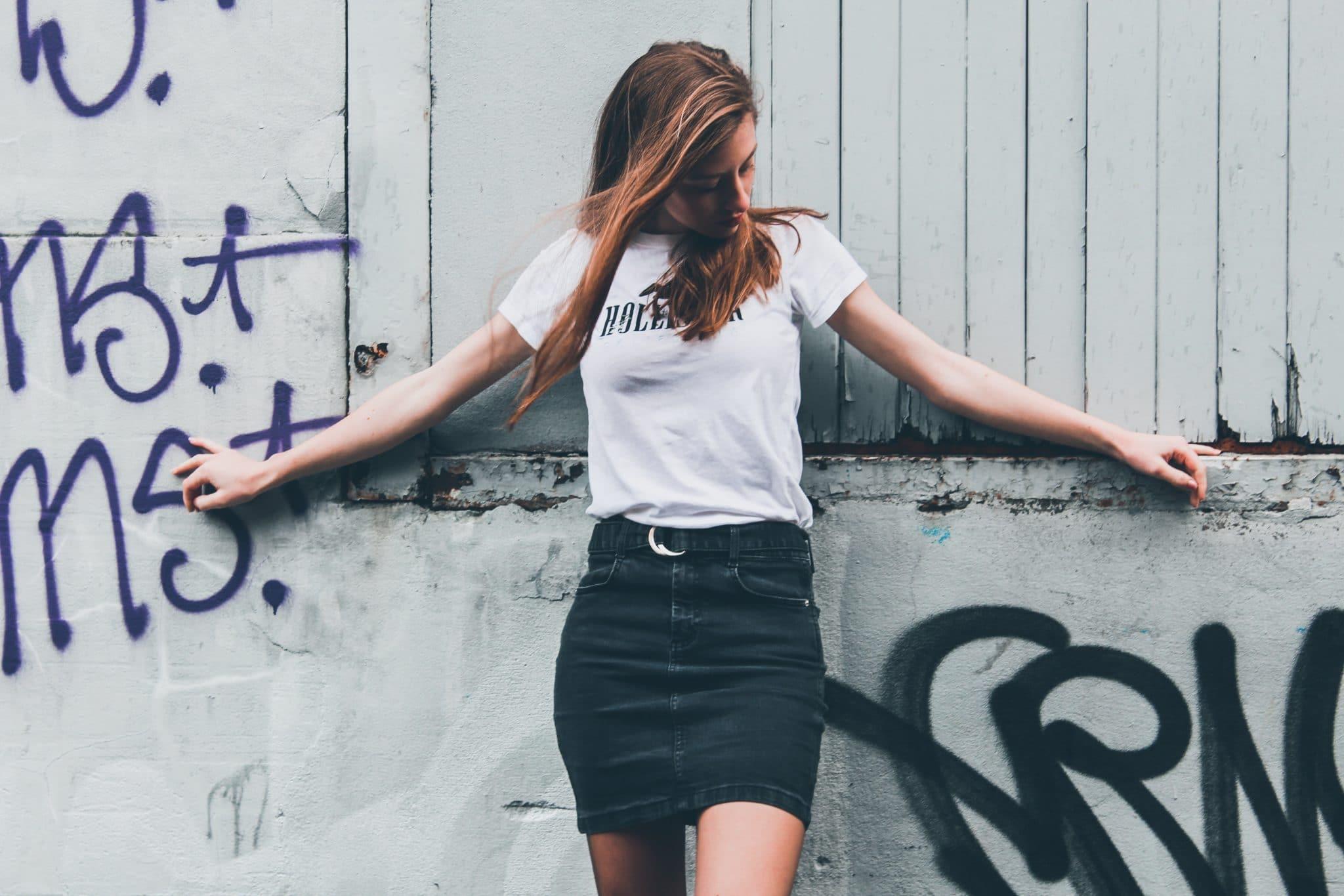 Jupe crayon tendance porté par une femme appuyée contre un mur